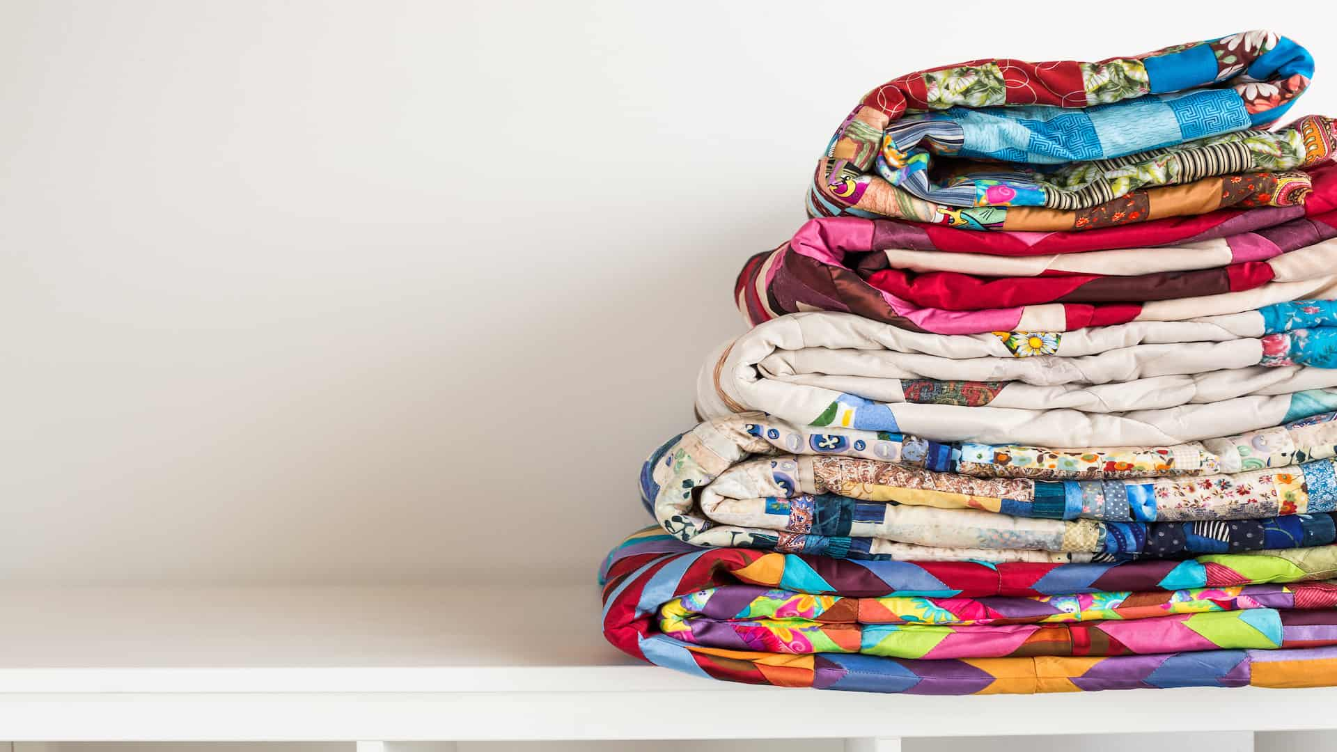 sewing and fashion concept - stack of colorful quilts, beautiful bedspreads stacked in several rows in height for storage, sale patchwork productions on a white background, copy space.