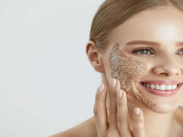 Face Skin Care. Closeup Portrait Of Beautiful Happy Smiling Female With Cleansing Facial Scrub Mask On Cheek. High Resolution