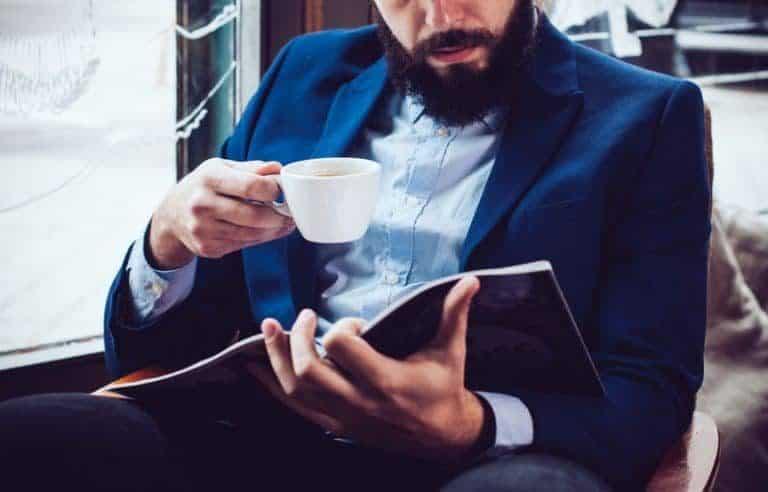 Caballero escuchando música y leyendo revista para relajarse