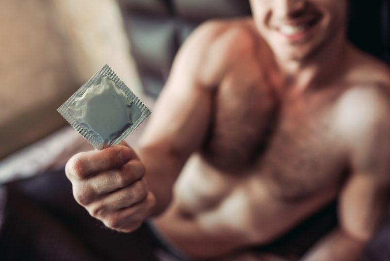 El preservativo masculino se enrolla en el pene erecto antes de la relación sexual
