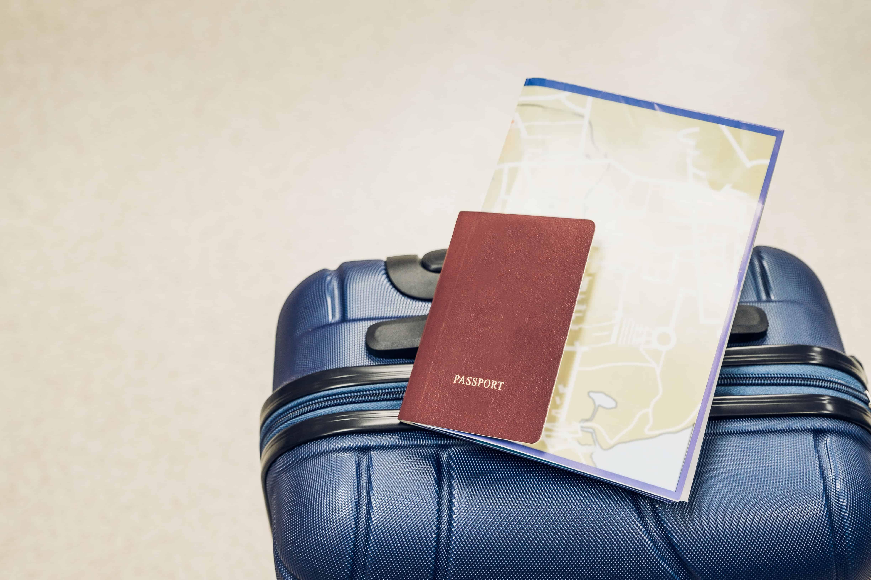 Persona lista para viajar con maleta y pasaporte