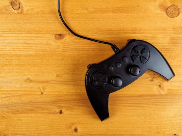 Gamepad controller on wooden desk, flat lay top view, gaming and entertainment concept with copy space