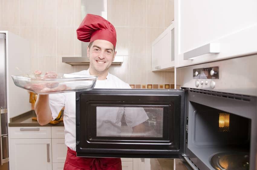 chef-kok koken met magnetron in de keuken