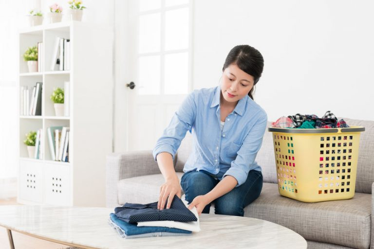 smiling pretty housewife foldinging clean clothing
