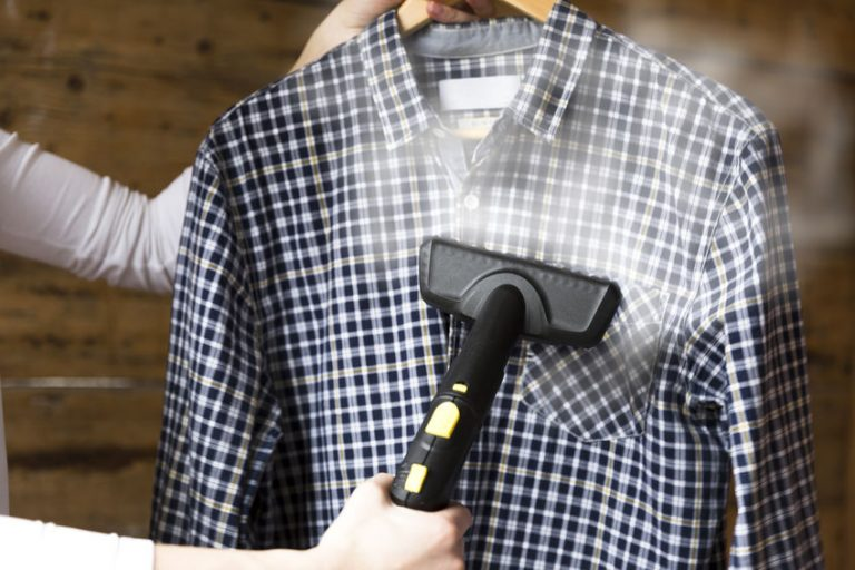 Woman ironing shirt with garment steamer