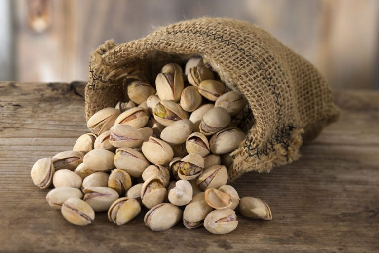 roasted and salted pistachios pour out of a burlap bag