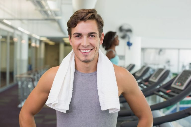 Handsome man smiling at camera beside treadmills at the gym