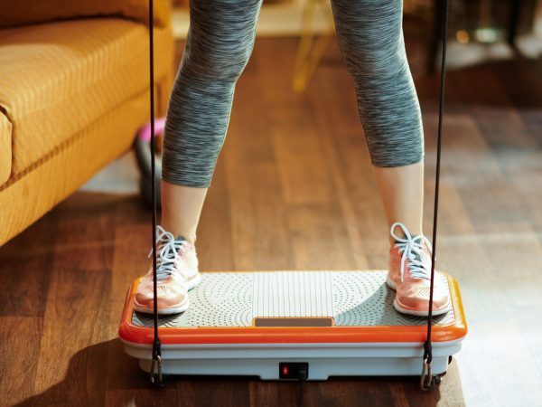 Closeup on sports woman training using vibration power plate