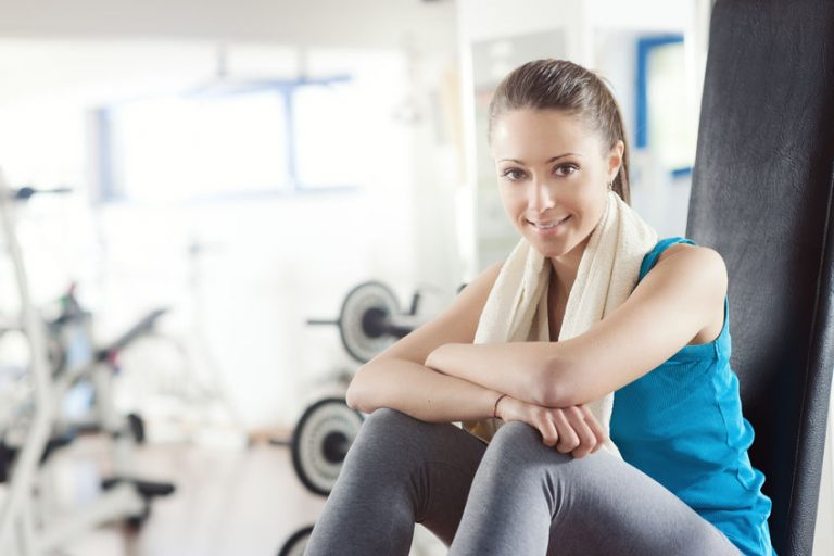Smiling woman at gym relaxing on exercise bench
