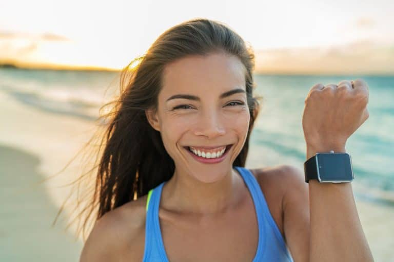 Smiling girl on the beach with trackin watch