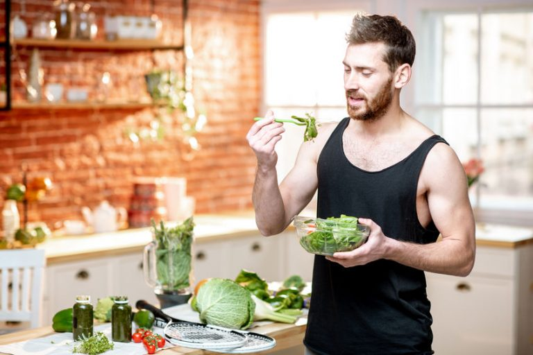 Fitness man eating a salad
