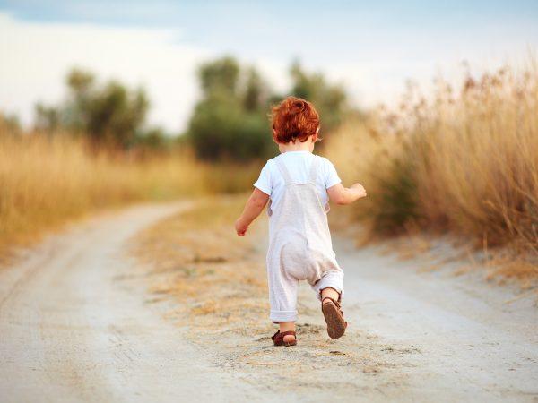 cute toddler baby boy running away along the path at summer field
