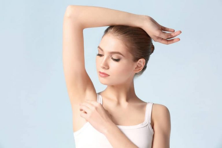 beautiful girl shaving her armpits