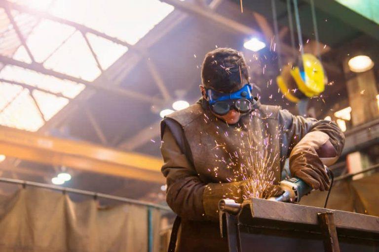 a man cutting iron pieces
