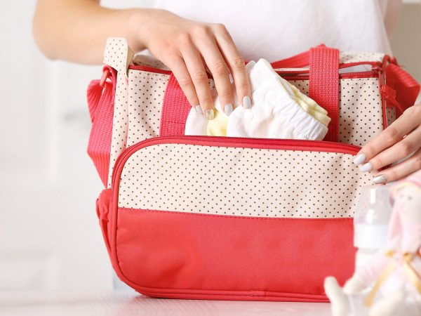 Woman packing her bag with child stuff