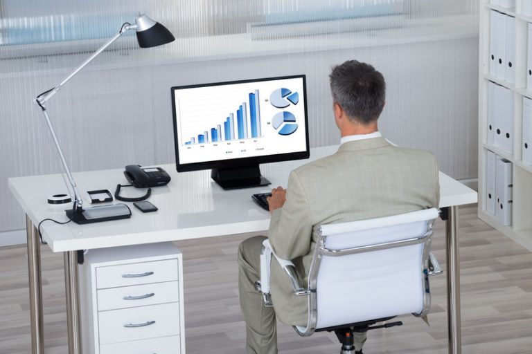 Businessman Analyzing Financial Graphs On Computer At Desk