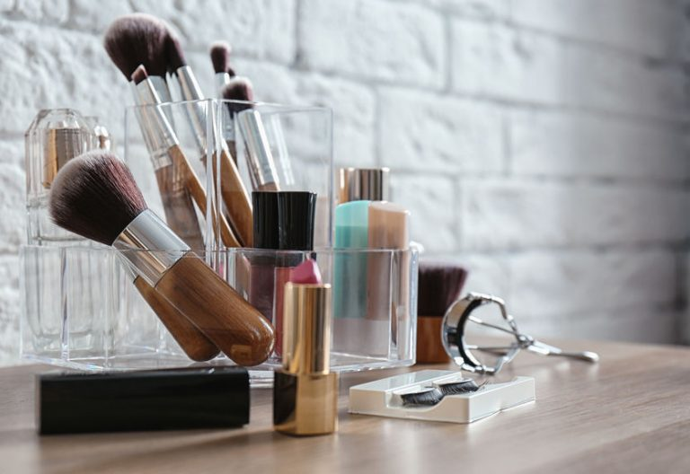 Organizer with cosmetic products for makeup on table near brick wall