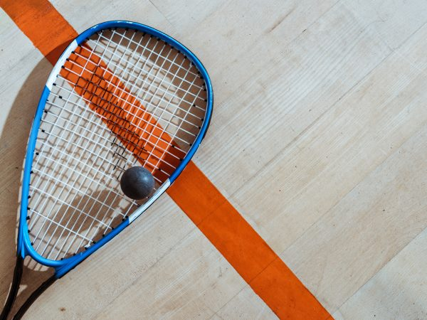 Top view of squash racket and ball on wooden surface