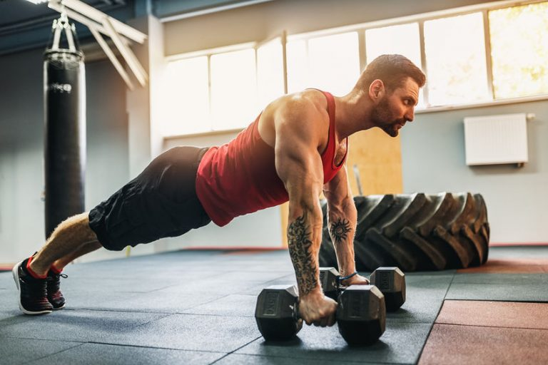 Muscular man doing pushup exercise with dumbbell in a crossfit workout
