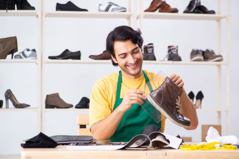 Young man repairing shoes in workshop