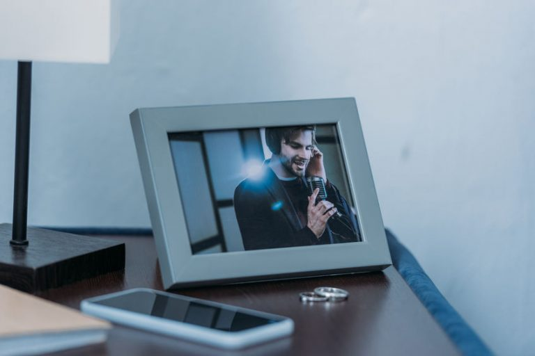 selective focus of photo frame with picture of man, marriage rings and smartphone on table