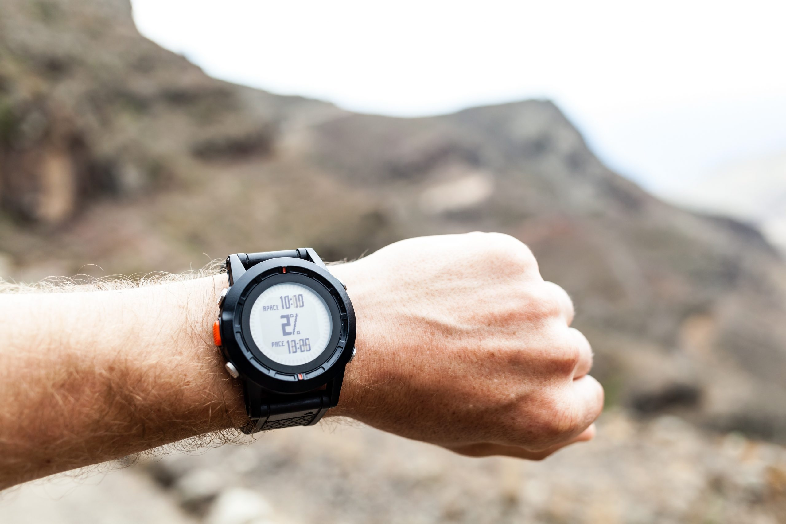 runner on mountain trail looking at sportwatch