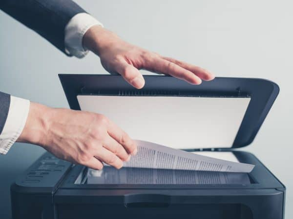 The hands of a young businessman is placeing a document on a flatbed scanner in preperation for copying it