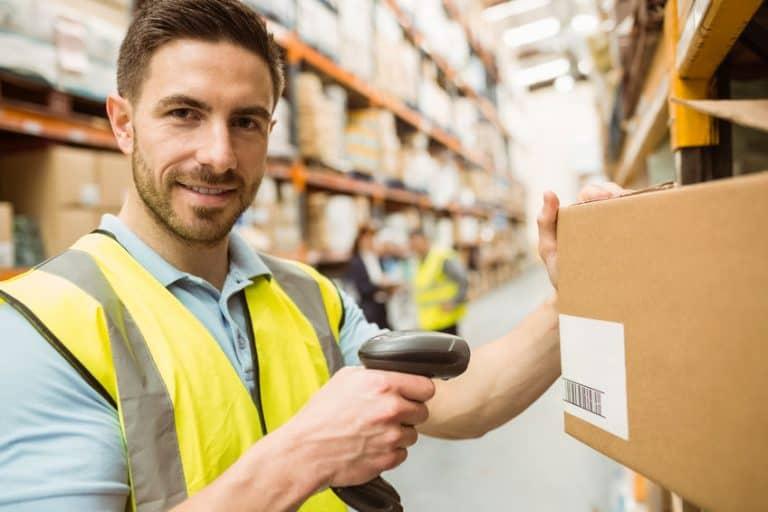 Trabajador de almacén escaneando cuadro mientras escanea producto con escaner de código de barras