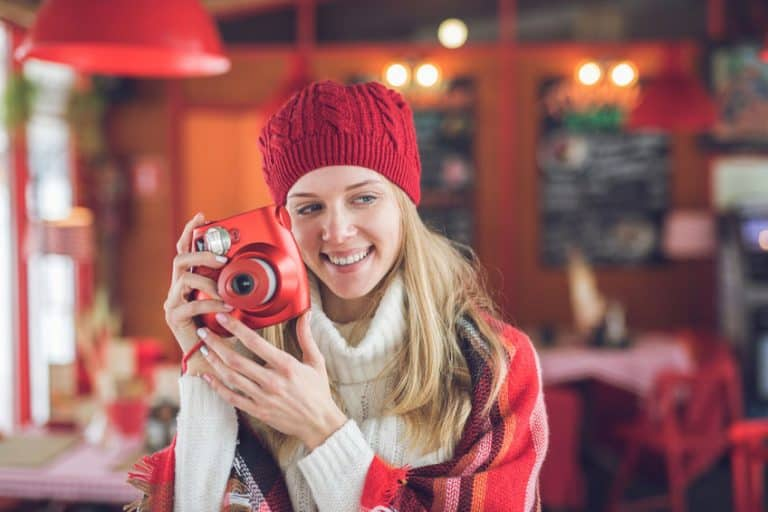 blonde woman in red cap holding a camera