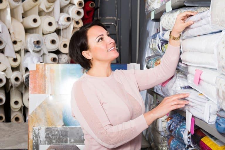 Customer handles bedspread near textiles