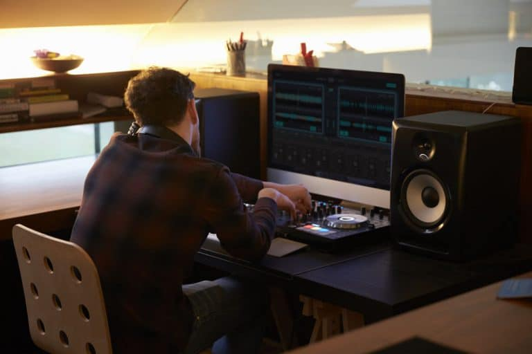 Man Composing Music on Computer in Bedroom
