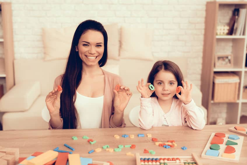 Woman and Girl Sitting with Toy Numbers in Hands.