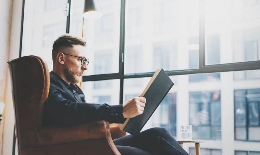Portrait handsome bearded businessman wearing glasses,black shirt.Man sitting in vintage chair modern loft studio, reading book and relaxing. Blurred background.Horizontal, film effect.