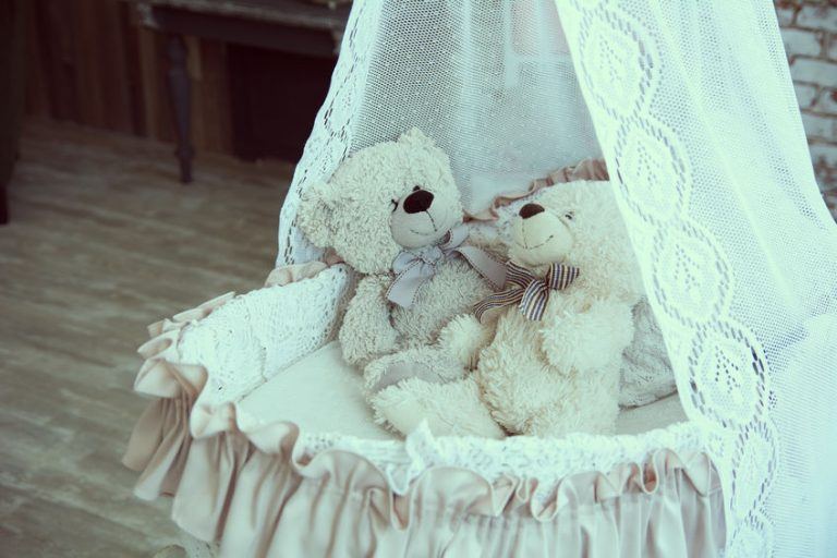 Baby cot with teddy bears on a background of a brick wall and wooden floor. Children's room in retro style