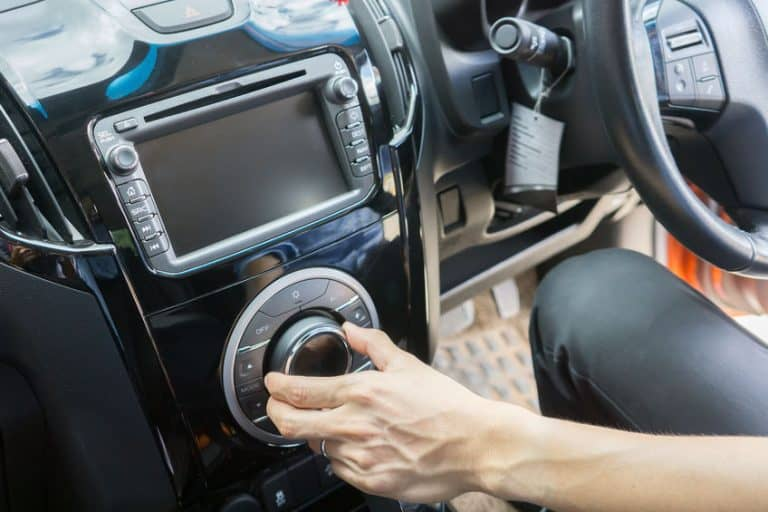 transportation and vehicle concept - sound stereo systems,Businessman hand driving a car , Male sit inside control volume audio system Finger lie on wheel Empty copy space ,vintage color