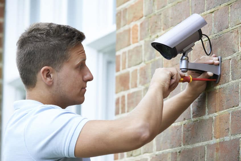 Security Consultant Fitting Security Camera To House Wall