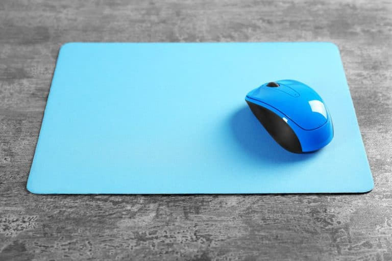 Blank mat and wireless mouse on textured background