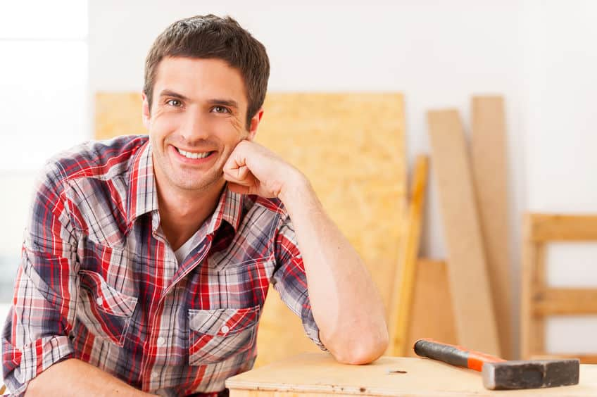 Taking time to relax. Handsome young handyman smiling while sitting in workshop and leaning at the wooden deck