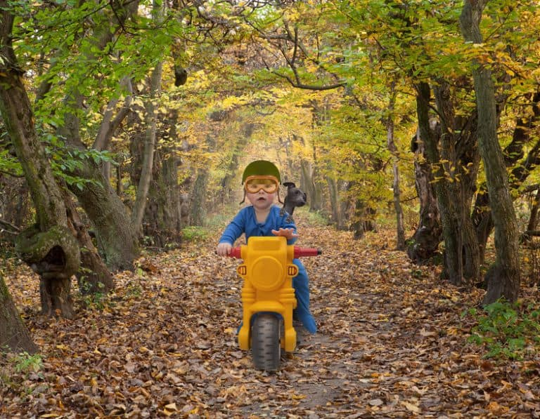 little kid riding a motorbike toy