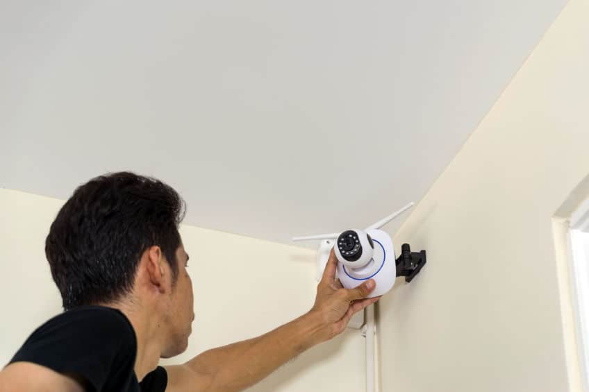 Technicians are installing a wireless cctv camera on the roof, can connect to the Internet, and control the camera via a smartphone or tablet.