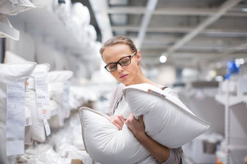 Pretty, young woman choosing the right pillow for her bed in a m