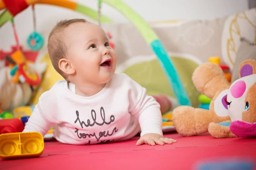 Eight months old baby girl playing with colorful toys on a floor