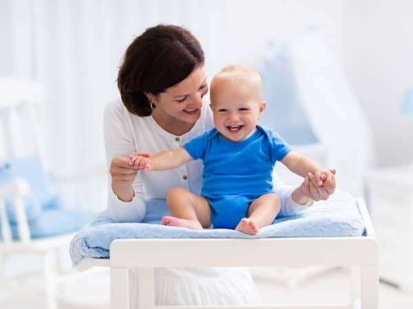 Young mother taking care of little boy in white sunny nursery with changing table, baby crib and rocking chair. Diaper change and clothing. Mom and son in beautiful bedroom at home.