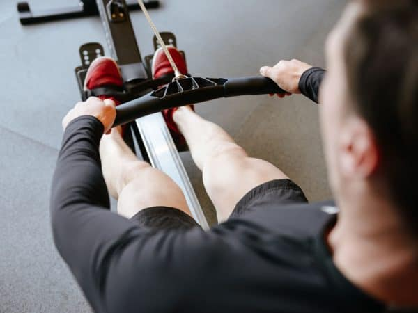 Back view of Athletic man using rowing machine