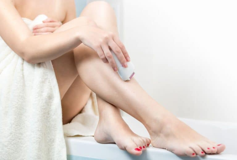 Young woman epilating legs after having bath