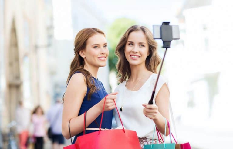 happy women with shopping bags and smartphone