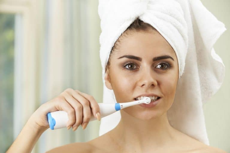 Woman Brushing Teeth With Electric Toothbrush In Bathroom