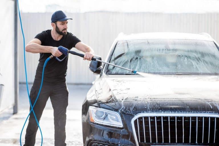 Man washing car with water gun