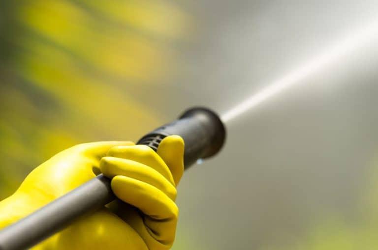 Closeup black head of high pressure water cleaner as waterbeam emerges