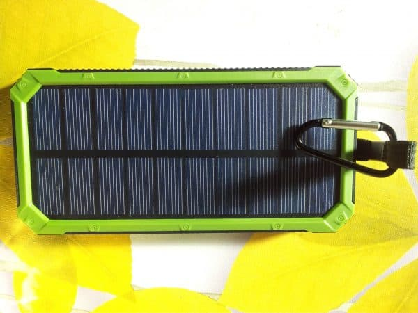 Charger Solar on green background with white USB cord for Charging smartphone phone from the solar battery.